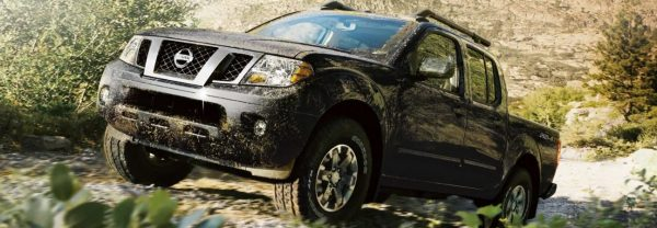 Black 2019 Nissan Frontier climbing gravel path