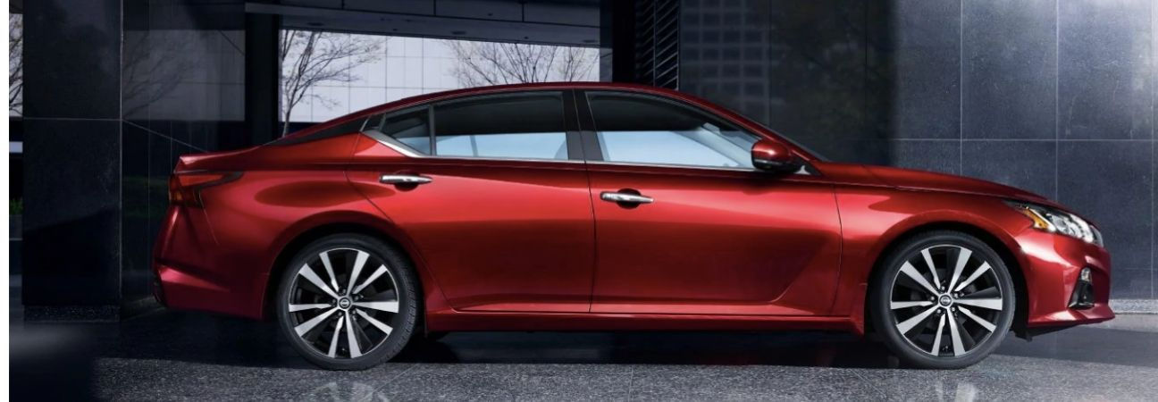 Red 2019 Nissan Altima parked in front of a modern office building.